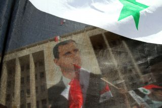 Syrians in Damascus on March 29, 2011, wave their national flag and hold portraits of President Bashar al Assad during a rally to show support for their leader in the wake of dissent.