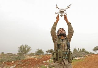 A Turkey-backed Syrian rebel fighter launches a drone.