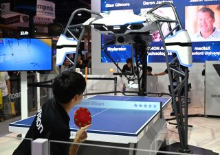A man plays table tennis with the Omron Orpheus AI table tennis tutor robot at CES 2019 consumer electronics show on Jan. 8.