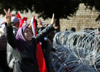 A protester pleads with soldiers to allow her through the razor wire barricade outside the Tunisian prime minister's office on Jan. 24, 2011 in Tunis.