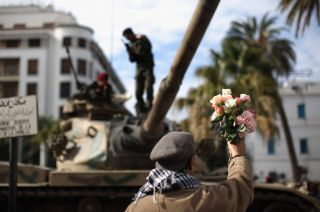 A protester offers flowers to soldiers on Jan. 21, 2011 in Tunis during a three-day period of mourning for the people who died during the country's revolution.