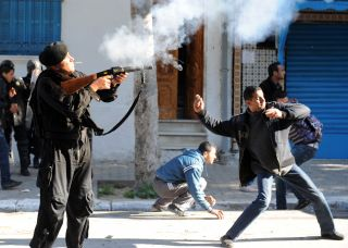 A Tunis resident throws a stone while a police officer shoots a tear gas canister on Jan. 26, 2011 in front of former Prime Minister Mohammed Ghannouchi's office.