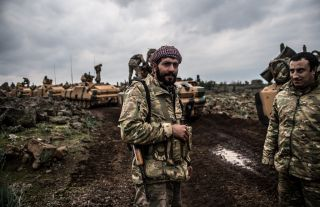 A soldier stands in front of Turkish army tanks preparing to enter Syria on Jan. 21.