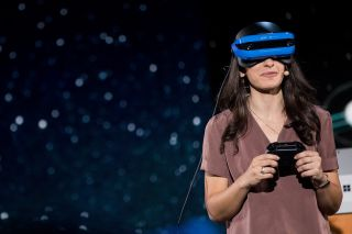 An employee from Microsoft demonstrates the company's new virtual reality headset at an event in May 2017.