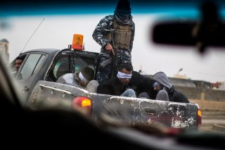 Christian militia fighters from the Nineveh Plain Protection Units drive a pickup truck in Qaraqosh, Iraq, transporting four alleged members of the Islamic State on Dec. 20, 2016.